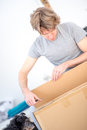 Man unpacking a cardboard carton in casual clothes kneeling on the floor flat tilted angle close up view Royalty Free Stock Photo