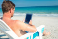 Man using digital tablet on deck chair at the beach a sunny day Stock Images
