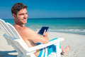 Man using digital tablet on deck chair at the beach a sunny day Royalty Free Stock Photos