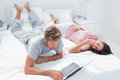 Man using a laptop next to his wife lying on bed in the bedroom Royalty Free Stock Images