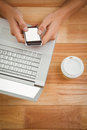 Man using mobile phone while laptop and disposable cup on desk overhead view of in office Royalty Free Stock Image