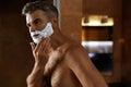 Man Using Shaving Cream On Face In Bathroom. Men Skin Care Royalty Free Stock Photo