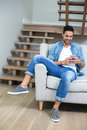 Man using smartphone while sitting on sofa Royalty Free Stock Photo