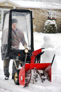 Man using snowblower uisng in his home entryway during a winter blizzard Royalty Free Stock Photography