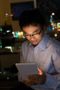 Man using tablet at night asian in the office Royalty Free Stock Image