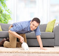 Man vacuuming with a handheld vacuum cleaner young carpet and smiling at home shot tilt and shift lens Royalty Free Stock Photography