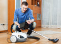 Man  vacuuming with vacuum cleaner on parquet floor in living ro Stock Photo