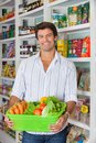 Man with vegetable basket in supermarket portrait of happy mid adult male customer Royalty Free Stock Photos