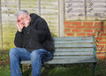 Man very stressed on verge of a panic attack sitting bench with his hands to his face and feeling the is the Royalty Free Stock Image