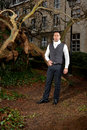 Man in victorian clothing in the park front of a house and trunks of trees Stock Images