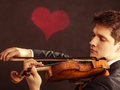 Man violinist playing violin classical music art and artist young elegant in love fiddler on black background with valentine heart Stock Images