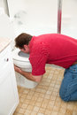 Man vomiting in toilet kneeling down the bathroom into the Stock Images
