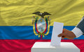 Man voting on elections in ecuador putting ballot a box during fornt of flag Stock Photo
