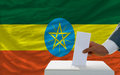 Man voting on elections in ethiopia putting ballot a box during fornt of flag Royalty Free Stock Photos