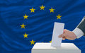 Man voting on elections in europe putting ballot a box during fornt of flag Royalty Free Stock Images