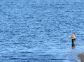 A man in waders fishing from in the water at leighton reservoir north yorkshire Royalty Free Stock Image