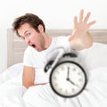 Man waking up late for work early throwing alarm clock funny bed concept with young oversleeping Royalty Free Stock Images