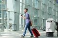 Man walking at airport with suitcase and mobile phone Royalty Free Stock Photo