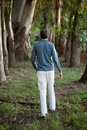 Man walking alone in woods rear view of the Stock Photo