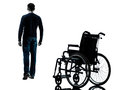 Man walking away from wheelchair silhouette one in studio on white background Stock Photo