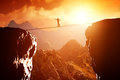 Man walking and balancing on rope over precipice