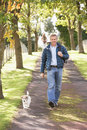 Man Walking Dog Outdoors In Autumn Park Stock Photos