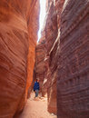 Man walking down narrow canyon a walk on a dry stream bed that cuts through red sandstone and forms a small in vermillion cliffs Royalty Free Stock Image