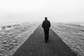 Man walking on an empty desolate raod away Royalty Free Stock Image