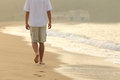 Man walking and leaving footprints on the sand of a beach back view at sunset Royalty Free Stock Photos