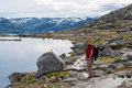 Man walking on a mountain trail in Norway. Path to Trolltunga or Royalty Free Stock Photo