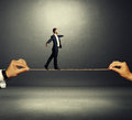 Man walking on the rope over dark assured businessman background Royalty Free Stock Photo