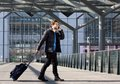 Man walking with suitcase and mobile phone at airport Royalty Free Stock Photo