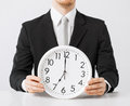 Man with wall clock close up of holding Stock Images