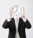 Man with wall clock covering his face Stock Images