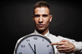 Man with wall clock over dark background Stock Image