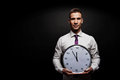 Man with wall clock over dark background Royalty Free Stock Photography