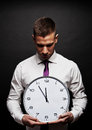 Man with wall clock over dark background Stock Photo