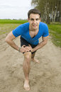 Man warm up frontal wide angle shooting of a young in a blue t shirt short black shorts and barefoot in low posture forward bent Royalty Free Stock Photo