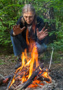 Man is warming his hands at the fire in forest Stock Images
