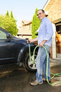 Man washing car on driveway Royalty Free Stock Images