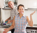 Man washing plates in home kitchen housewife at and her husband Stock Images