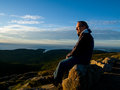 Man watching the sunrise over the sea on top of cadillac mountain in acadia national park Stock Photography