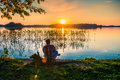 Man watching sunset adult by the lake Stock Photo