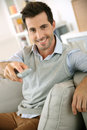 Man watching tv at home smiling young Royalty Free Stock Image