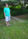 Man watering his grass lawn Stock Images
