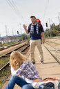 Man waving to woman sitting on railroad Royalty Free Stock Photo