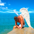 Man wearing angel wings muscular with on the beach Stock Image