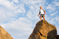 Man wearing a backpack on a high rock standing top of in the summer sunshine looking down at the camera Stock Photo