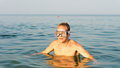 Man wearing goggles swimming in the sea standing chest high saltwater summer sun while enjoying his vacation Royalty Free Stock Image