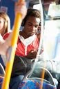Man wearing headphones listening to music on bus journey with a bag his lap Stock Photography